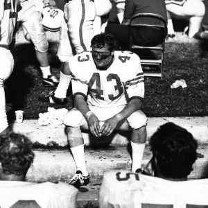 North Carolina State University defensive back Jim Smith sitting on sidelines during game.