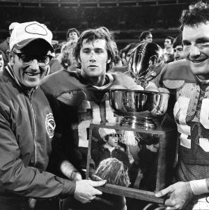 Head coach Lou Holtz, flanker Pat Kenney (25), and defensive back Tom Siegfried (45) posing with Peach Bowl Champions trophy following 49-13 win over West Virginia in Atlanta, Georgia, December 29, 1972.