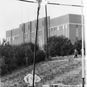 NC State track team member and ACC champion Stuart Corn pole vaulting in track field behind Reynolds Coliseum