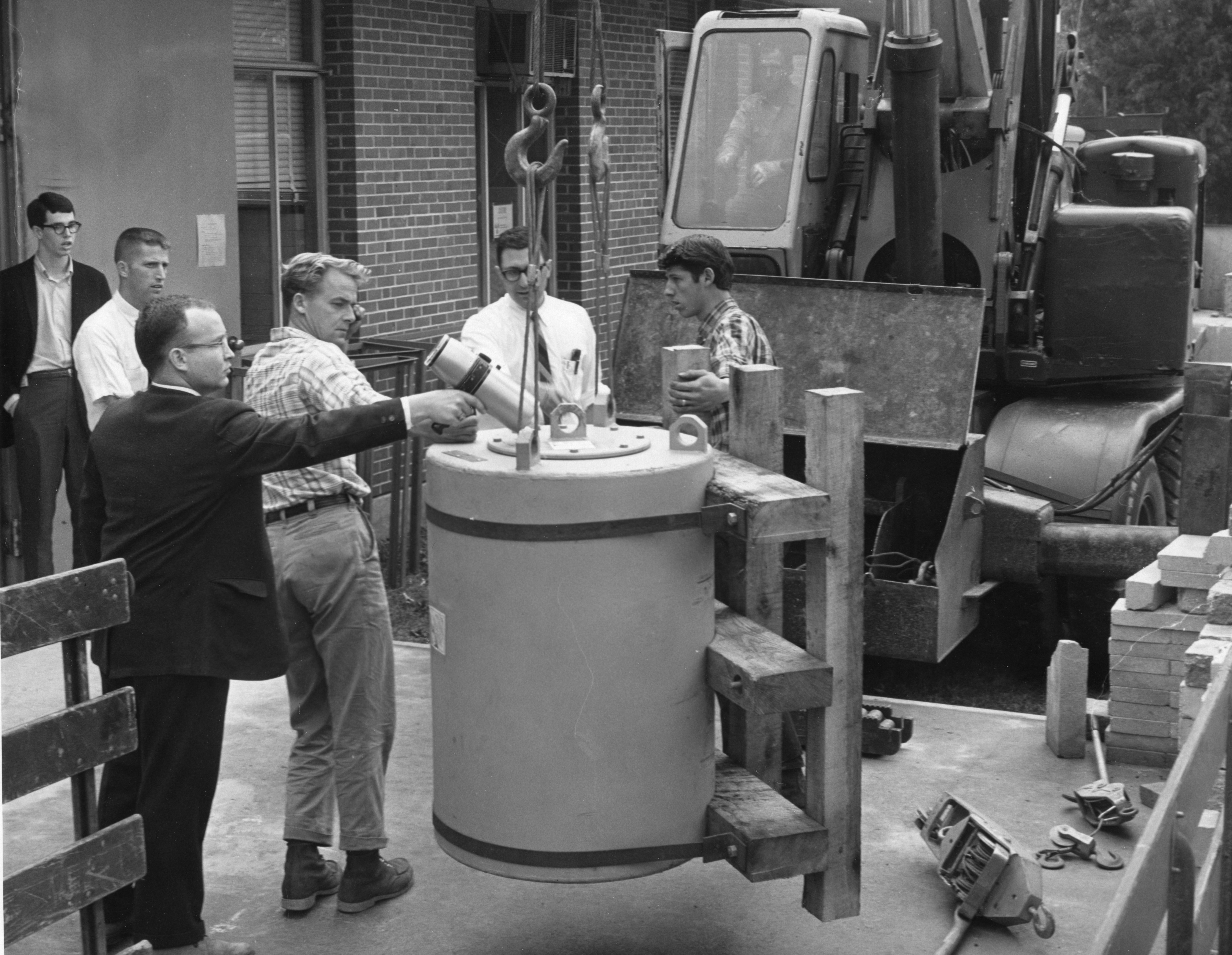 Group of men receiving a shipment of fuel for the nuclear reactor at Burlington Engineering Laboratories, North Carolina State College