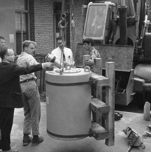 Group of men receiving a shipment of fuel for the nuclear reactor at Burlington Engineering Laboratories