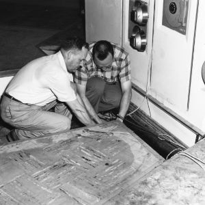 Professors E. J. Brown and Joseph T. Lynn adjusting the sampling system of the nuclear reactor
