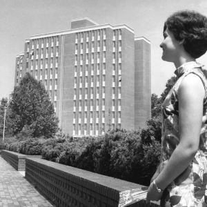 Woman in front of Carroll Residence Hall, the new woman's dorm