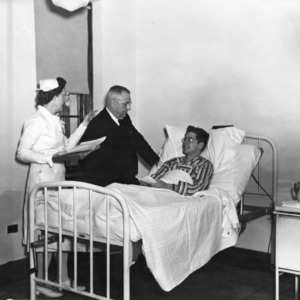 Nurse and other standing at patient's bedside in Clark Infirmary