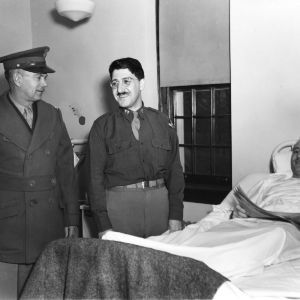 Two military officers standing at patient's bedside in Clark Infirmary