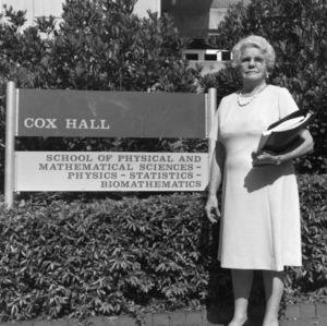 Gertrude Cox standing in front of Cox Hall