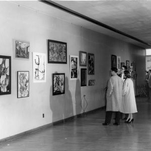 Visitors viewing paintings in art gallery