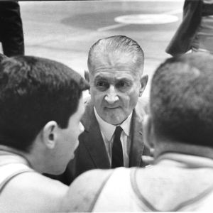 North Carolina State University basketball coach Everett Case kneeling in front of players bench.