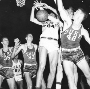 All-America center Ronnie Shavlik (84) fighting for basketball in North Carolina State's 80-77 win over Duke in 1955 ACC championship.