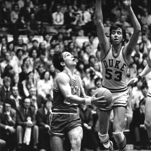 North Carolina State University basketball player Monte Towe driving for a layup in game against Duke.