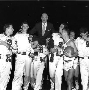 North Carolina State College basketball players lifting coach Everett Case on their shoulders after winning 1955 Atlantic Coast Conference championship.