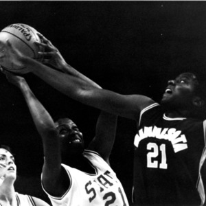 North Carolina State University's Ronnie Laughlin and Minnesota player reaching for basketball