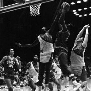 North Carolina State University's Genia Beasley watching teammate Ronnie Laughlin shooting the ball against two University of North Carolina defenders.