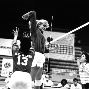 North Carolina State University All-American volleyball player Pam Vehling leaping above net.