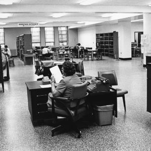 Secretary and students in D. H. Hill Jr. Library.