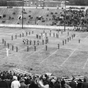 View of North Carolina State College marching band in formation at Riddick Stadium.