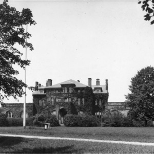 Distant view of Holladay Hall with cannon and flagpole in foreground, North Carolina College of Agriculture and Mechanic Arts.