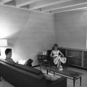 Husband and wife reading in living room of married student housing unit at McKimmon Village, North Carolina State College