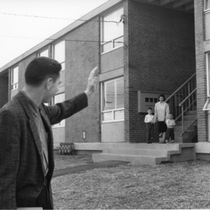 Husband waving to his wife and children outside of McKimmon Village housing unit for married students, North Carolina State College