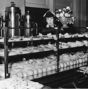Cafeteria line worker standing behind display of desserts and salads in Leazar Hall, North Carolina State College