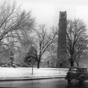 Winter view of Memorial Tower, with automobile on Hillsborough Street in foreground, North Carolina State College