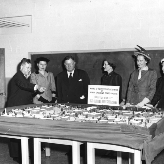 "Chancellor John Harrelson showing group of unidentified people a ""model of proposed future campus of North Carolina State College"" on display in Riddick Engineering Laboratories."