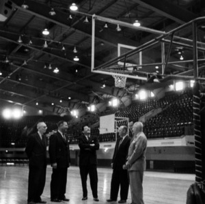 Men standing on the basketball court in Reynolds Coliseum