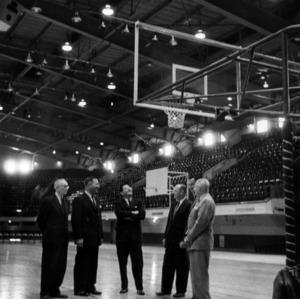 Men standing on the basketball court in Reynolds Coliseum