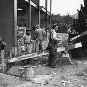Workers pour concrete to form the basement walls of Reynolds Coliseum, December 8, 1948.