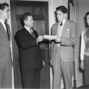 W. L. Woodall of Smithfield (second from right), chairman of the Student Government Commitee on Memorial Tower, presenting check to Chancellor J. W. Harrelson, president of the State College Foundation