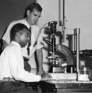 Eric L. Ellwood and student at microscope