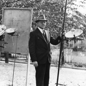 Charles M. Heck posing with his invention for measuring heat to forecast temperature change