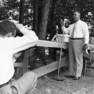 Frank H. Jeter speaking into radio microphone at outdoor event