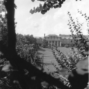 View looking through trees across Court of North Carolina toward 1911 Building, North Carolina State College