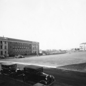 View looking northwest toward Polk Hall with automobiles parked in foreground and rear of Patterson Hall in distance, North Carolina State College
