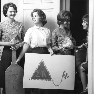 Four members of Sigma Kappa with a poster and paddle showing the sorority's insignia, North Carolina State University, September 1965.