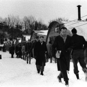 Students walking through snow past uninsulated Quonset huts that served as temporary classrooms at NC State after World War II