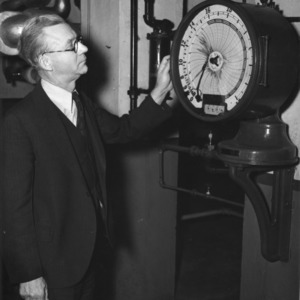 A. A. Riddle, Chief Engineer of NC State Power Plant, with meter