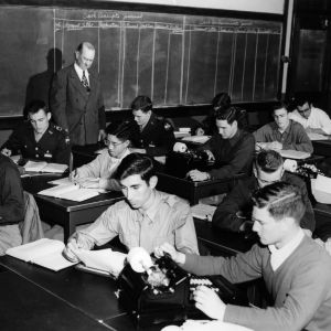 Teacher examining students at desks with adding machines