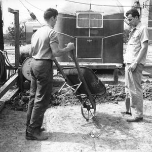 Two unidentified men, one with wheelbarrow, standing behind Trailwood mobile home, North Carolina State College, March 1946.