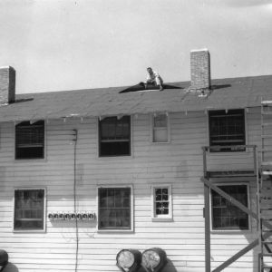 Man on roof of temporary classroom building.