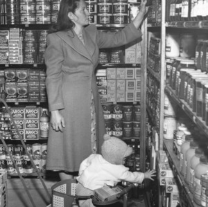 Woman and her child examining goods in the Vetville Mutual Grocery Co-op in the basement of Vetville YMCA.