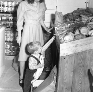 Mrs. Paul H. Rogers, of Hartsville, South Carolina, and her son Paul III, select some vegetables at the Vetville Mutual Grocery, Inc., newly established business for State College's married students.