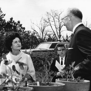 Lady Bird Johnson, Dean H. Brooks James, and a student reporter examining plants
