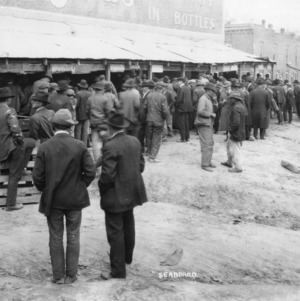 View of men gathered outside hog auction, Wadesboro, North Carolina, March 15, 1923.