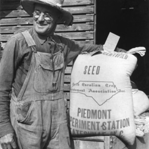 Farmer posing with bag of seed from Piedmont Experiment Station, Statesville, North Carolina, 1941.