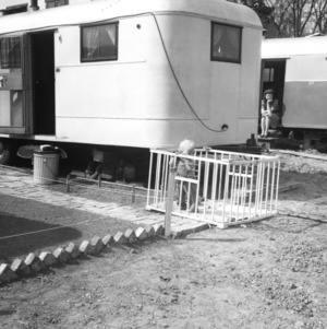 Small child in playpen outside of trailer being watched by woman seating on steps of neighboring trailer, Trailwood, North Carolina State College, March 1946.