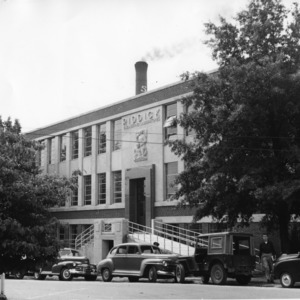View of Riddick Engineering Laboratories, North Carolina State College, cars parked in front.