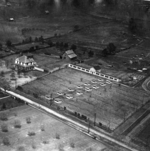 Aerial view of Agricultural Experiment Station farm near North Carolina State College campus showing poultry houses and Hillsborough Street.
