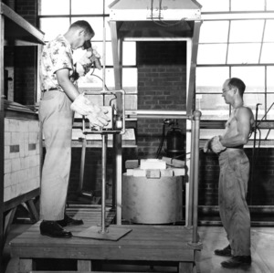 Thermal treating of specimens which have undergone vibration tests, Richard D. Dillender, research engineer (left) checks the kiln temperature, (right) George Boenshain, laboratory assistant, 1952 Summer